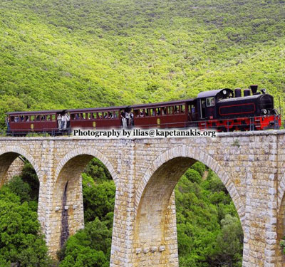 Train of Pelion crossing bridge behind Hiron Kentavros